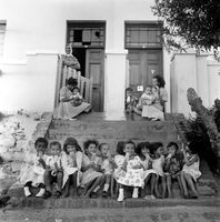 Group of young children eating ice-cream on the stairs, District Six, Cape Town, South Africa