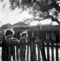 Young girls standing at a fence in District Six, Cape Town, South Africa