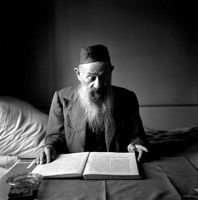 Bearded man reading at a table inside his home in District Six, Cape Town, South Africa