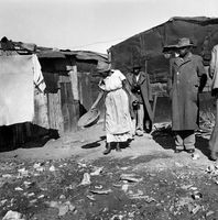 Residents standing outside their shacks, District Six, Cape Town, South Africa