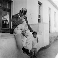 Man sitting on wall with his young son, District Six, Cape Town, South Africa