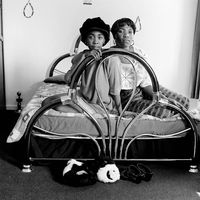 Two woman on a bed in their apartment, Johannesburg, South Africa