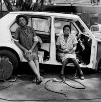 Residents of the Mai Mai hostel sitting in a scrap car, Johannesburg, South Africa