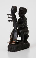 Figurine-man holding shoulder harp