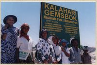 Members of the San community pose in front of a Kalahari Gemsbok Park sign