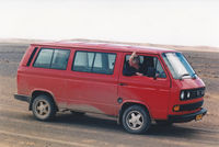 Hugh Brody driving a red minivan