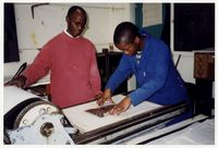Sipho Hlai assists a student with the printmaking press