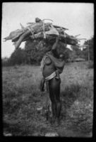 Mother carrying child and wood