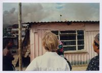 Val Goldschmit watches a shack burn in section 4 during a voter-education visit in Jan 1994