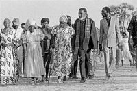Sam Nujoma walking with a group of people