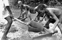 Children, orphans of the Angolan Civil War, pan for diamonds