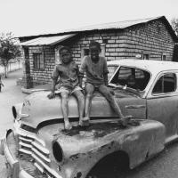 Young boys sitting on car wreck, Mafikeng, South Africa, 1981