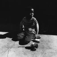 Young boy with home-made toys, Dinokana, South Africa, 1981