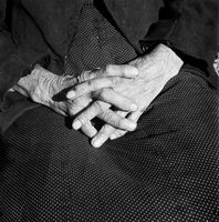 Elderly woman's hands crossed on her lap