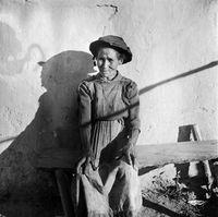 Elderly woman sitting on a bench, Genadendal, South Africa