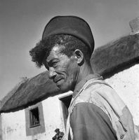 Portrait of a farm worker standing outside a thatched building, Genadendal, South Africa