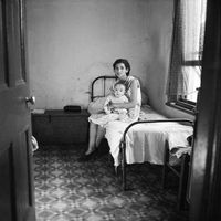 Mother and baby sitting on a bed, Genadendal, South Africa
