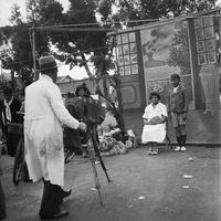 Man taking a studio portrait of a woman and her son, Genadendal, South Africa