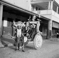 Zulu ricksha puller transporting customers.