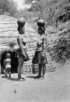 Zulu women conversing in front of their hut