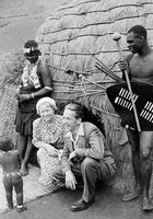 Europeans posing within a traditional Zulu setting