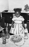 Little girl on her third birthday with cake and Oros, Eastern Cape, South Africa