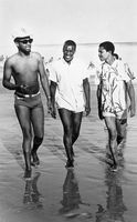 Three men walking along the shore, Eastern Cape, South Africa