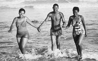 Man holding hands with two women as they walk out the sea, Eastern Beach, South Africa