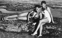 Two women posing on a rock next to the ocean. Eastern Beach, Eastern Cape, South Africa