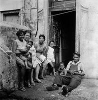 Family sitting outside their home, District Six, Cape Town, South Africa
