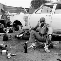 Man sitting in front of a scrap car, Mai Mai hostel, Johannesburg, South Africa