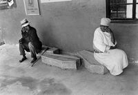 Man and woman sitting on child-sized coffins, Transkei, South Africa