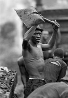 Man holding a spade above his head, South Africa