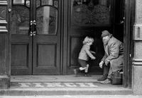 Man and child in a doorway, England