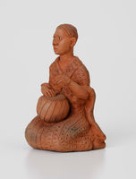 Figurine of a woman playing a moropa drum
