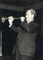 Prof. Kirby sounding the fascimile of the (?) Egyptian trumpet, the original of which is in the Louvre. On the table is his copy of the bronze trumpet of Tut-ank-hamen. This photograph